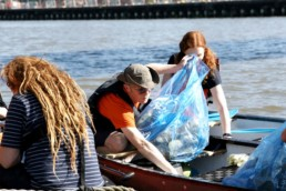volunteers filling a rubbish bag on the river Lea