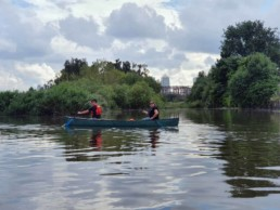 Photo of volunteers canoeing past Canary Wharf overlooking an island in the channel